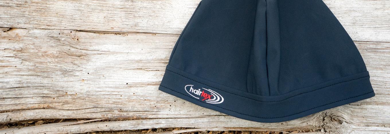 hairtex Stall-Mütze mit Bändern in grau vor einem Holzbrett.