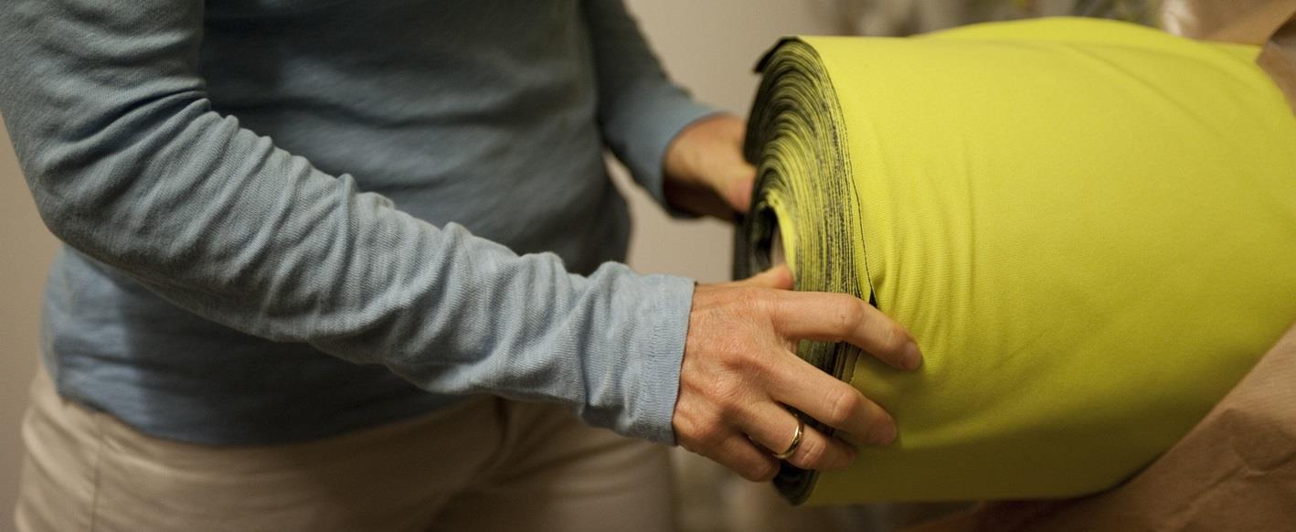 Frau nimmt popgrünen Stoff aus Regal