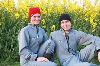 Frau und Mann mit hairtex Stallbekleidung sitzen vor einem blühendem Rapsfeld.