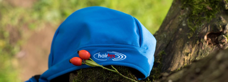 hairtex Stall-Mütze mit Bändern liegt auf einem Ast mit einer Hagebutte.