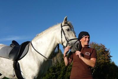 Frau mit einer hairtex Stallmütze mit Bändern steht neben einem Pferd